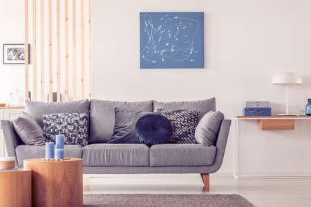 Interior de la elegante sala de estar escandinava con pintura azul en la pared y mesa de consola con lámpara