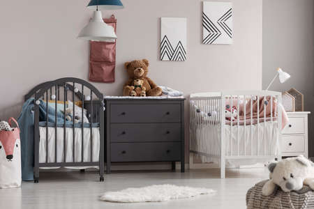 Grey wooden commode in the middle of cute baby room for twins
