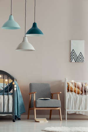 Pastel lamps above stylish vintage armchair in the middle of cute baby room for twins