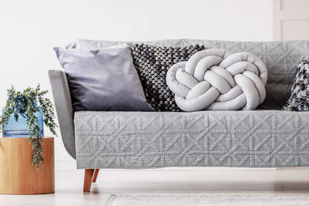 Trendy knot light grey pillow on comfortable scandinavian couch