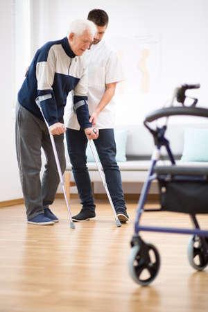 Starszy mężczyzna chodzący o kulach i wspierający go pomocny pielęgniarz