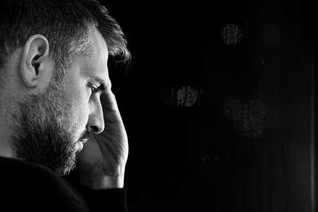 Kopieer de ruimte op een zwarte achtergrond naast het gezicht van een bezorgde man met een probleem