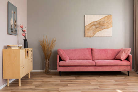 Flowers in vases on wooden commode in contemporary living room interior with pastel pink sofa Фото со стока