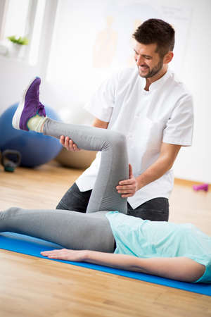 Mujer de mediana edad haciendo ejercicio sobre una alfombra azul durante la fisioterapia con un joven médico