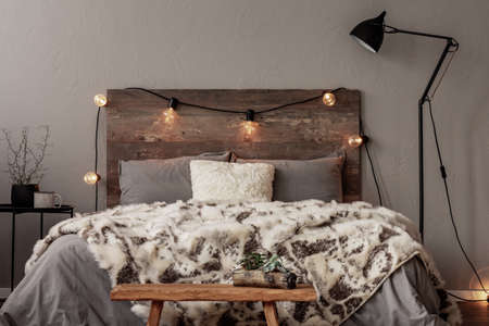 Light bulbs on wooden headboard of comfortable bed with grey bedding and warm fury blanket Reklamní fotografie