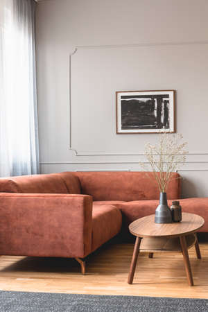 Dry flowers in stylish dark vase on wooden coffee table in front of ginger colored corner sofa