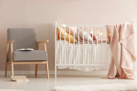 Open book on retro armchair next to white wooden crib with pastel bedding