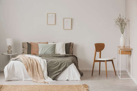 Stylish chair next to warm king size bed in scandinavian bedroom