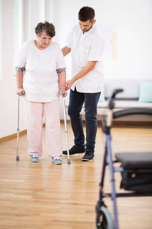 Senior woman at hospital learning how to walk on crunches and supporting male nurse Stok Fotoğraf