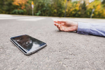 Close-up of mans hand and broken phone on the road Фото со стока
