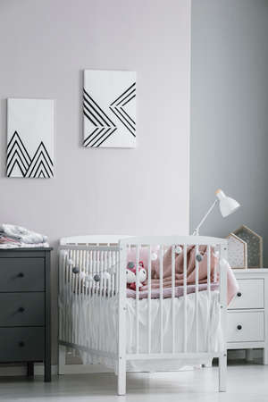 White crib with paste pink bedding and cotton balls in bright bedroom interior