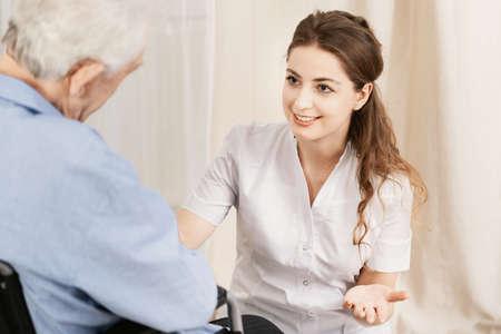 Junger hilfsbereiter Arzt mit älterem Mann im Rollstuhl Standard-Bild