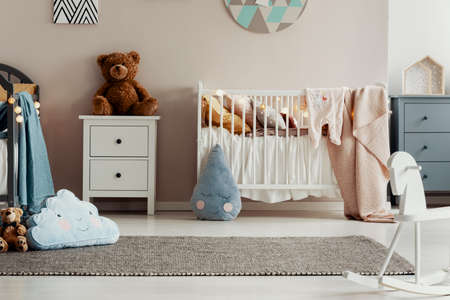 White wooden furniture in pastel scandinavian baby bedroom for twins Stock Photo