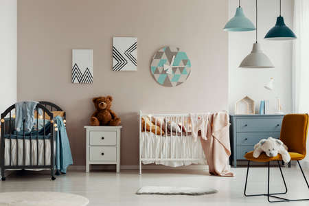 Chic baby bedroom with wooden cribs, lamps, white wooden nightstand with brown teddy bear and fashionable yellow chair