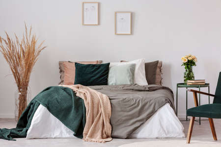 Colorful pillows in king size bed with duvet and blankets in hygge inspired bedroom 版權商用圖片