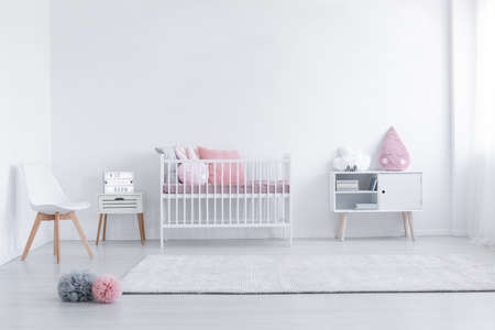 Pink pillow on cabinet and white chair in simple kids room interior with carpet and cradle. Real photo Stock Photo