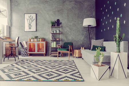 Real photo of living room interior with cactuses, grey sofa, big lamp, geometric carpet and texture wall