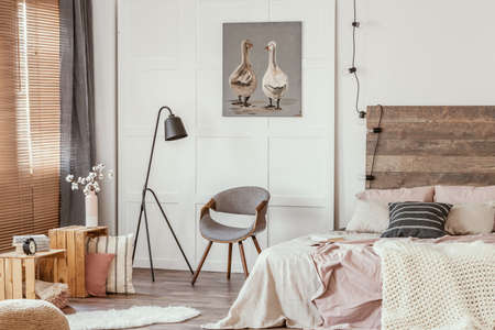 Black industrial lamp next to stylish grey wooden chair in the middle of delightful bedroom interior