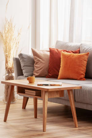 Retro wooden coffee table in front of grey couch in classy living room interior Stock Photo - 130625179