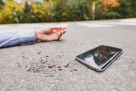 Man and his phone on the street after the accident 版權商用圖片