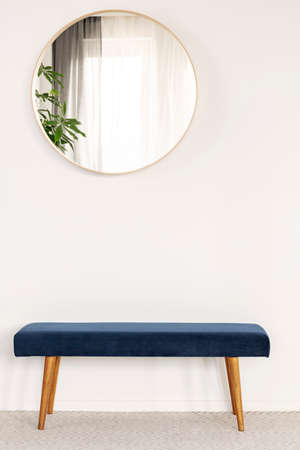 Round mirror in wooden frame on empty white wall of bright living room interior 免版税图像