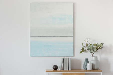 Peinture à l'huile abstraite bleu et blanc pastel sur un mur blanc vide avec console avec des fleurs dans un vase et des livres
