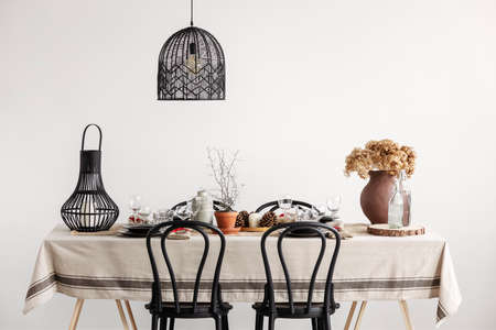 Black chairs, lantern and lamp in vintage dining room