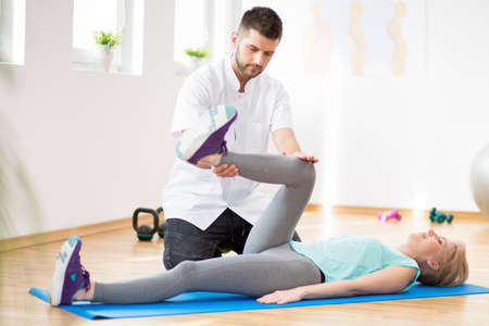 Middle age woman exercising on blue mat during physiotherapy with young male doctor Stock fotó