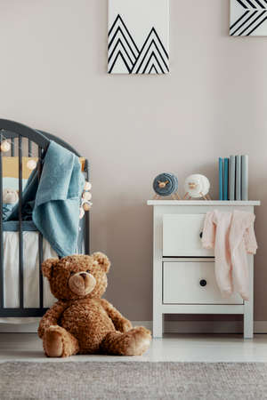 Brown teddy bear on the wooden floor of scandinavian baby bedroom interior