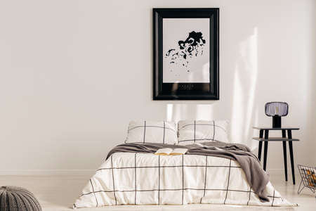 Black and white map in black frame in trendy bedroom interior with chequered bedroom Standard-Bild