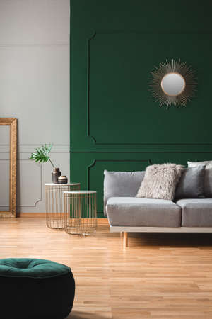 Emerald green living room interior with grey and golden accents