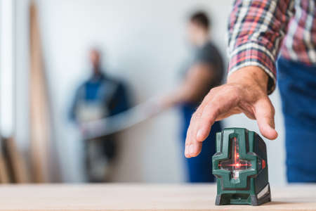 Close-up of builders hand reaching for a laser level