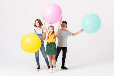 Three kids at the party playing with big balloons 版權商用圖片