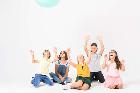 Happy school kids with hands up playing with the blue balloon