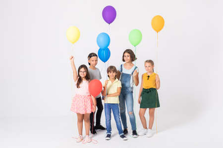 Happy school boys and girls holding colorful balloons Stockfoto