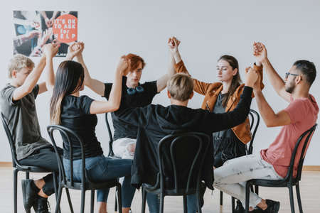 Group of teenagers holding their hands together on a therapy