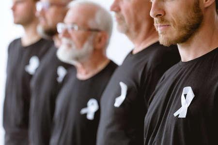 Group of men in black wearing white ribbon
