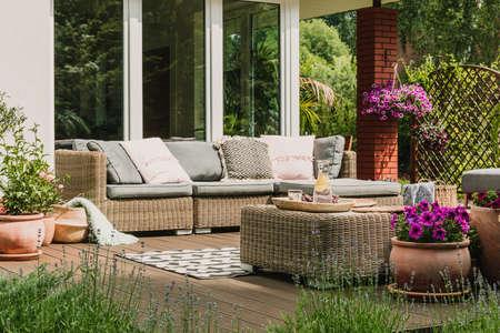 Classy furniture on wooden terrace in green beautiful garden 스톡 콘텐츠 - 131354229