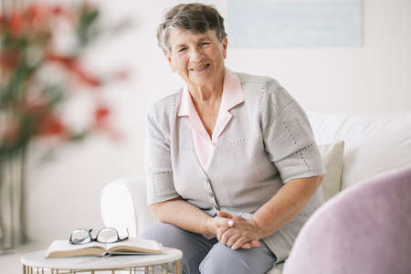 Happy older woman in a nursing house sitting in her room
