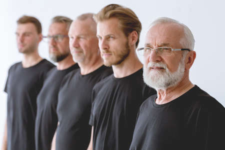 Group of men in different age wearing black standing in a row