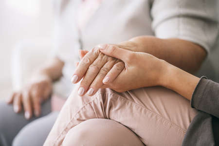 Close up of caregiver holding womans hand