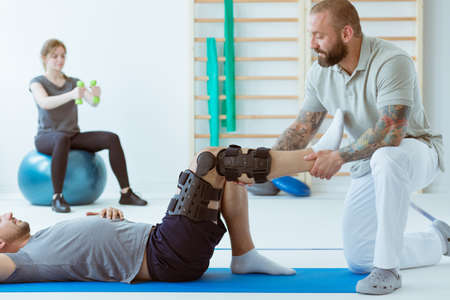 Teenage girl after car accident with orthosis on the leg exercises on blue mat in the company of physiotherapist Stockfoto