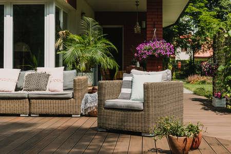 Cómodo sillón de mimbre con almohadas en la terraza de madera de la casa suburbana de moda Foto de archivo