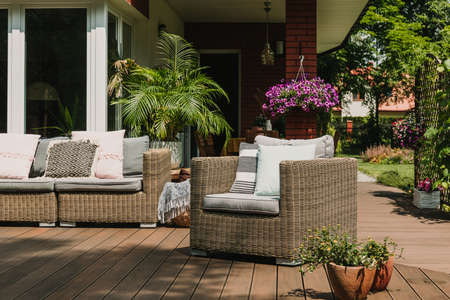 Comfy wicker armchair with pillows on wooden terrace of trendy suburban home Stock Photo