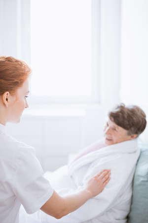 Elderly sick woman in nursing home and her caregiver Standard-Bild - 131354001