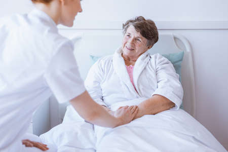 Young nurse taking care of older patient in a hospital Standard-Bild - 131354003