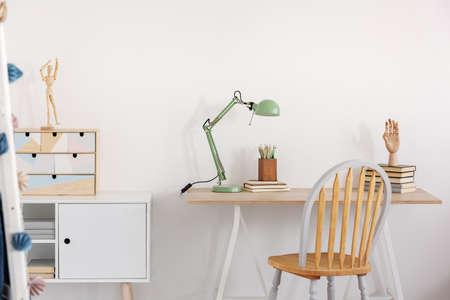 Pile de livres, main en bois et lampe industrielle de couleur menthe sur un élégant bureau en bois dans une chambre d'enfant blanche