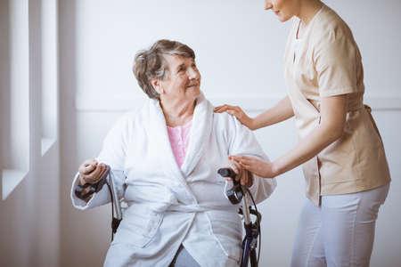 Older sick woman sitting on a walker in a hospital Standard-Bild - 131354144