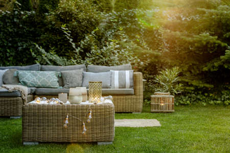 Modern designed garden with wicker seating set and coffee table