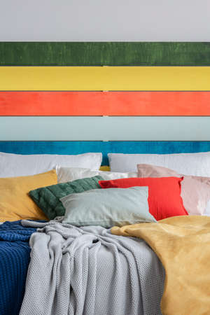Closeup of king size bed with green, yellow, red and grey pillows